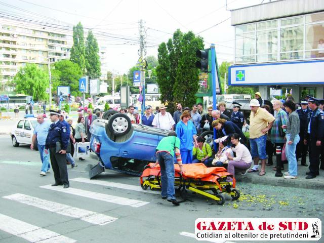 Şoferiţa (femeia aşezată pe bordură) a ieşit din maşina răsturnată pe geamul uşii din stânga faţă