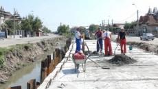 Muncitorii sunt o raritate pe strada Râului din Craiova, care urmează să fie modernizată cu fonduri europene.  În fotografie sunt cei 6-7 muncitori care încearcă să caseteze canalul colector de pe mijlocul străzii.