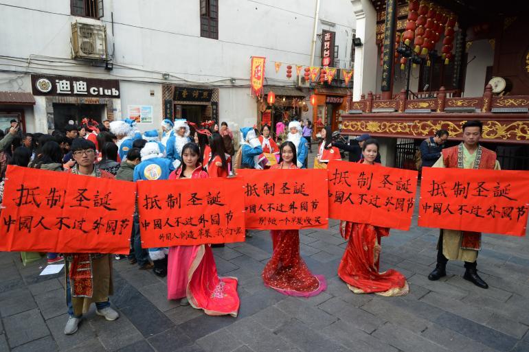 """Grup de protestari cu pancarte pe care scrie """"Împotriviţi-vă Crăciunului, cetăţenii chinezi nu ar trebui să sărbătorească festivaluri străine"""" (Foto: ibtimes.com)"""