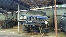 Lângă CAS Dolj, un autoturism Dacia zace într-o parcare, cocoțat pe câteva anvelope (Foto: GdS)