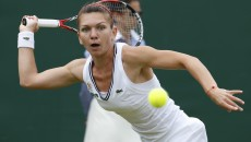 Simona Halep of Romania hits a return to Li Na of China during their women's singles tennis match at the Wimbledon Tennis Championships, in London