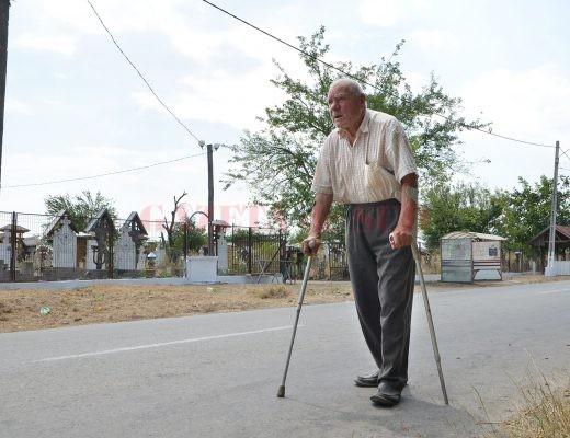 Gheorghe Giolea are 82 de ani, iar de trei ani nu a mai putut ajunge la mormântul fiului şi părinţilor din cauza buruienilor  din cimitir (FOTO: Bogdan Grosu)