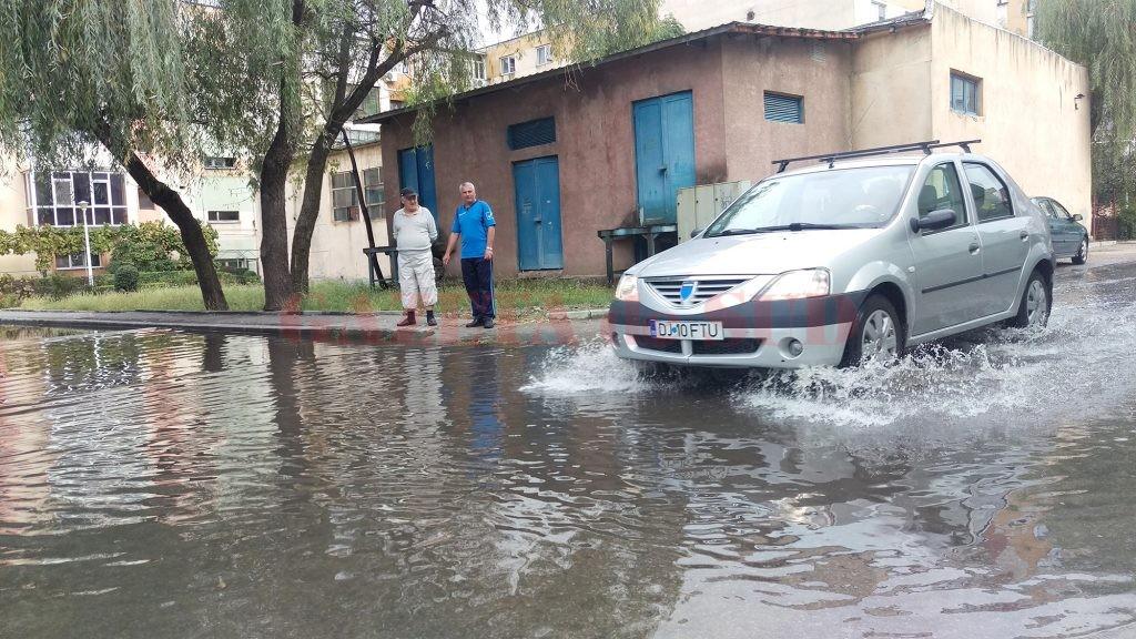 Parcarea din cartierul 1 Mai care s-a transformat în baltă, din cauza gurii de canal înfundate (Foto: Marian Apipie)