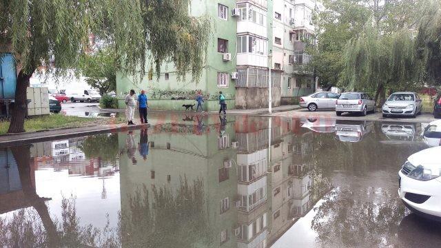 Parcarea din cartierul 1 Mai care s-a transformat în baltă, din cauza gurii de canal înfundate