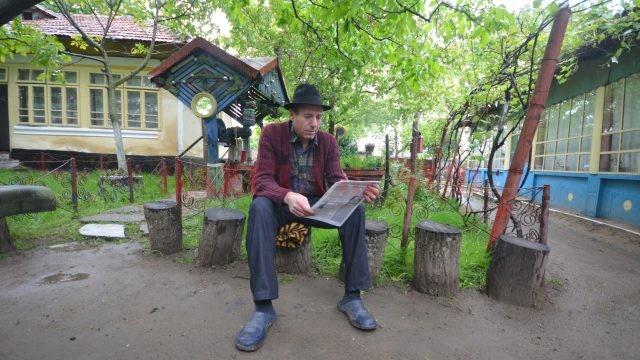 Pe un butuc vechi, tocit de ședere, în Poiana lui Iocan, Fane Roșioru își așteaptă mușterii (Foto: Traian Mitrache)