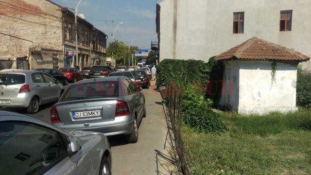 Mașini parcate pe trotuar, pe strada Matei Basarb