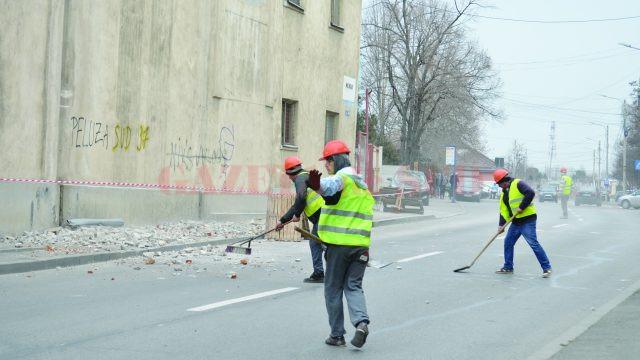 Lucrătorii făceau semne şoferilor să oprească, în timp ce excavatorul dărâma bucăţi din zidul morii (Foto: Bogdan Grosu)