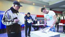 Un tânăr din Cârcea era cât pe ce să aplice ștampila pe buletinele de vot în afara cabinei de votare. El a fost observat la timp de președinta secției de votare și a fost trimis în cabina de vot să aplice ștampila, așa cum spune legea. (Foto: Bogdan Grosu)
