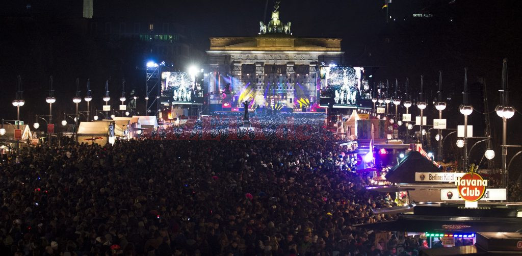Revelers crowd the avenue in front of Berlin's Brandenburg gate (background) on December 31, 2012, as they wait to usher in the New Year. AFP PHOTO / JOHN MACDOUGALL        (Photo credit should read JOHN MACDOUGALL/AFP/Getty Images)