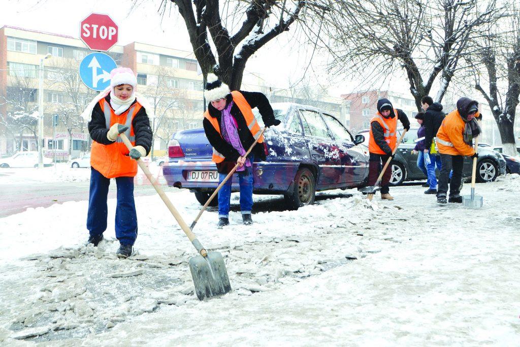 Angajații de la Salubritate înlătură zăpada de pe trotuarele bulevardului 1 Mai (Foto: Bogdan Grosu)