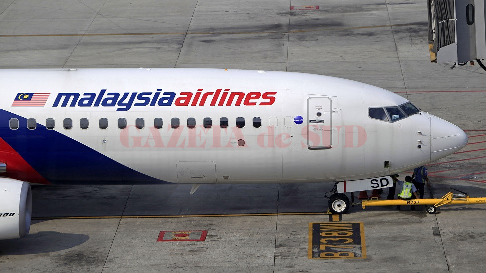 Ground staff take a break under a Malaysia Airlines plane at Kuala Lumpur International Airport in Sepang, Malaysia, Sunday, March 9, 2014. An international fleet of planes and ships scouted the waters between Malaysia and Vietnam for any clues to the fate of the Malaysia Airlines Boeing 777, which disappeared less than an hour after taking off from Kuala Lumpur bound for Beijing on Saturday, March 8. (AP Photo/Lai Seng Sin)