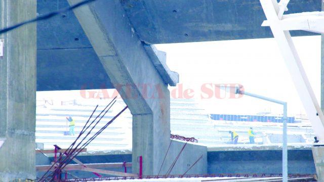 """La -12 grade Celsius, cât se înregistrau marți la prânz, la Stadionul """"Ion Oblemenco"""" se lucra: unii muncitori dădeau zapada din tribune, alții încărcau la materiale (Foto: Lucian Anghel)"""