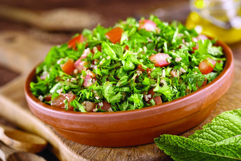 48886857 - a bowl of delicious fresh tabouli with parsley, mint, tomato, onion, olive oil, lemon juice, and bulgar wheat.