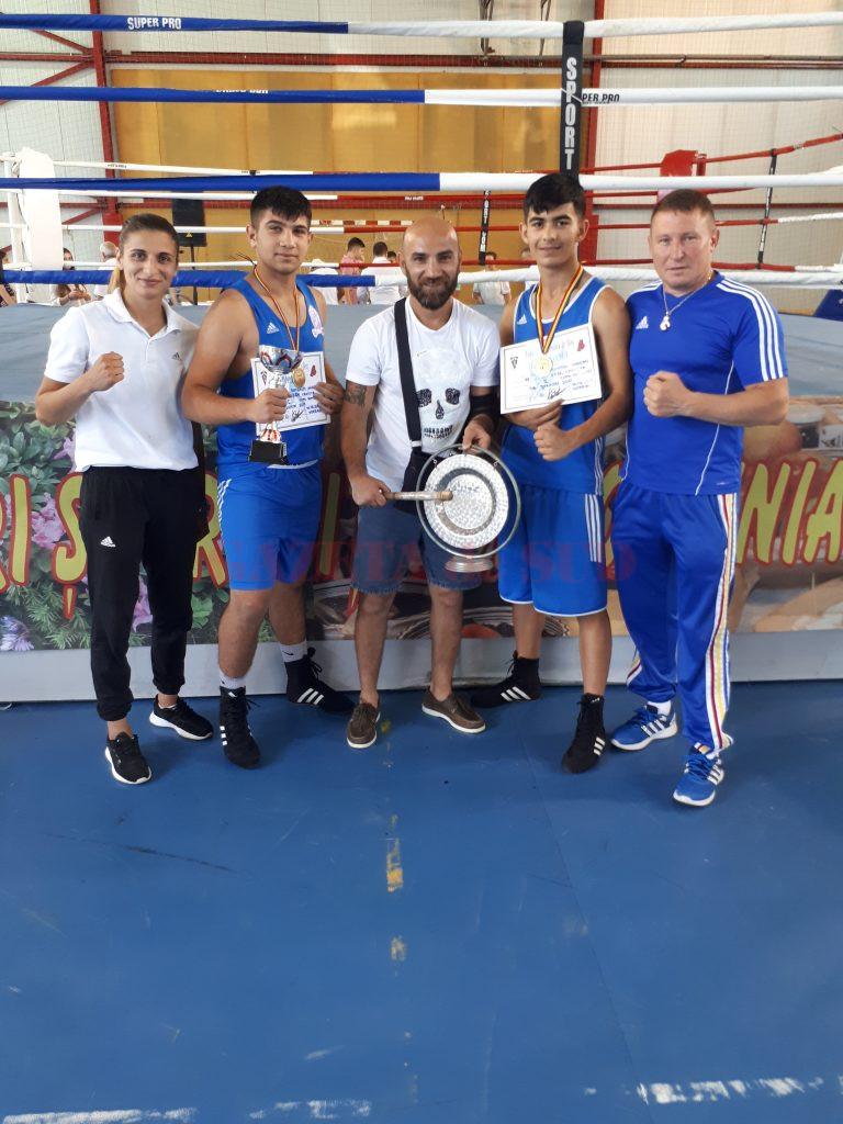 """Angelo Bambaloi (al doilea din stânga) a cucerit Cupa României, iar Bogdan Dumitru (al doilea din dreapta) a luat medalie de argint. Sportivii sunt antrenați de Dora Mustățea și Ion Dragomir (dreapta). Dumitru a fost ajutat în pregătire și susținut la competiție de Sorin """"Pantera"""" Tănasie (foto centru), campion mondial la juniori și campion european la profesioniști."""