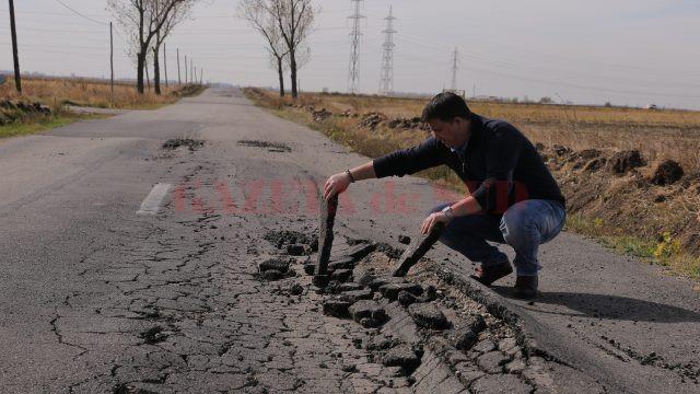 Drumul prezintă degradări serioase, din loc în loc existând suprafețe unde asfaltul s-a lăsat, a crăpat sau pare ca și cum ar fi explodat (Foto: Lucian Anghel)