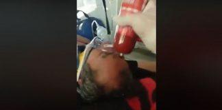 Un paramedic, filmat în timp ce loveşte cu un parizer un pacient inconştient