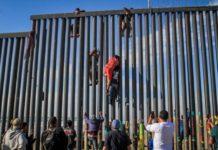 Imigranți sărind gardul în zona Tijuana, în statul mexican Baja California. Locul este preferat și de traficanții români care, împreună cu cei mexicani, reușesc să treagă ilegal mii de români peste graniță în SUA. FOTO: EPA