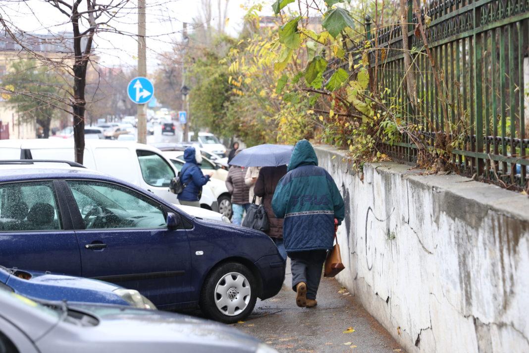Pietonii se strecoare cu greu printre maşinile parcate pe trotuar