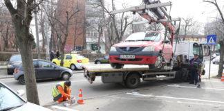"""Locuri rezidenţiale de parcare de pe Calea Bucureşti. Ieri se amenajau locurile din zona străzii Horia. Maşina de ridicări a dat """"o mână de ajutor""""."""